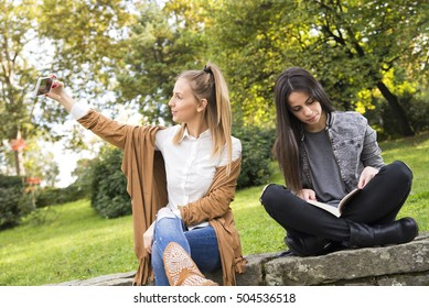 Two young student sitting in a park while reading a book and the other real common selfi.