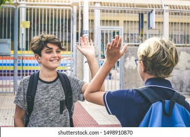 Two young students greet each other before the lessons. Happy boys with backpack meet out of institute after summer holidays the first day of school. Youth educational togetherness friendship concept.