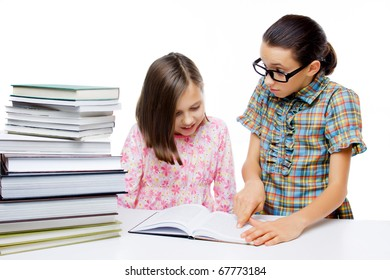 Two young students learning from a book, isolated on white
