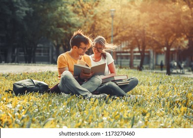 Two young students sitting at the campus yard , reading book and preparing for university exam.Autumn.