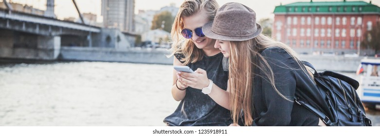 Two young stylish girls female teenagers 18 years old on the background of a European city and a river with a smartphone in their hands, panoramic banner