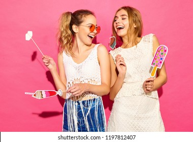 Two young stylish smiling blond women eating props sweet ice cream and fake cocktail.Positive models in summer hipster clothes posing near pink wall in studio in sunglasses