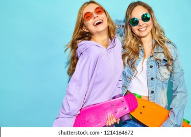 Two young stylish smiling blond women with penny skateboards. Girls in summer hipster sport clothes posing near blue wall in studio. Positive models