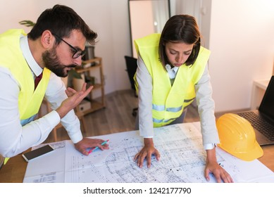 Two young successful architects and designers working hard on their project in the office, discussing the blueprint and a building project.