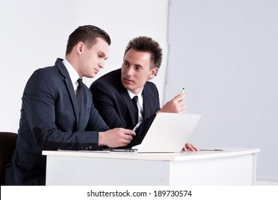 Two young and successful businessmen sitting at table and talking in office. Handsome men are sitting at laptop working on the tablet. Confident businessmen smiling  in formal wear and writing on paper