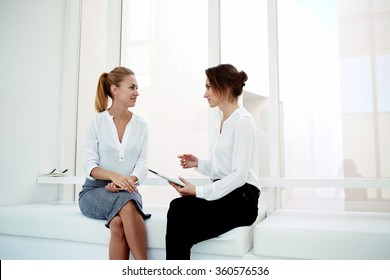 Two young successful female managing directors using digital tablet while discuss new business ideas, confident woman lawyers holding portable touch pad while talking with her clients in modern office