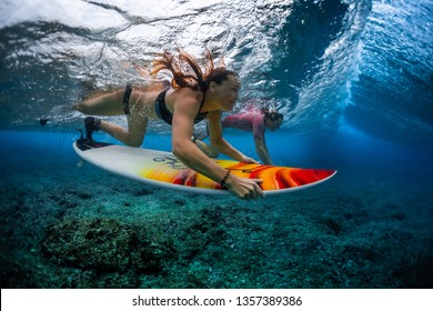 Two young surfers man and woman dive with their surfboards under the breaking ocean wave