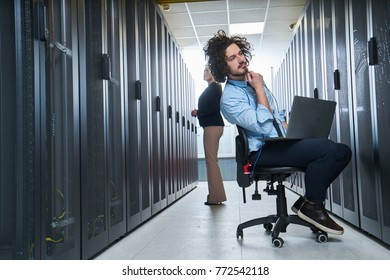 two young technicians working at a data center on server maintenance