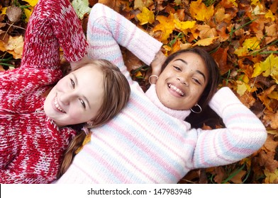 Two young teenager girls friends laying down with their heads together on a bed of autumn brown and yellow leaves, being joyful and laughing while having fun.