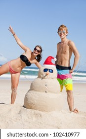 Two young teens having fun with Snowman made out of sand on beach during christmas. Escaping the cold travel concept.