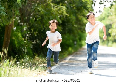 Two young Thai boy run together on the crack road in the natural park.