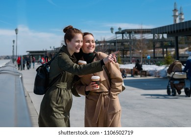 Two young travelers in fashionable coats and backpacks on the streets of Kazan. View attractions.