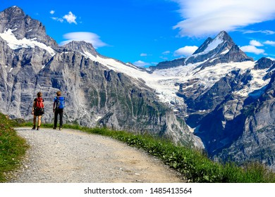 Two young traveller walking on the road trail at Grindelwald first, good viwe to see jungfruajoch.