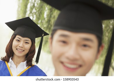 Two young university graduates looking at the camera