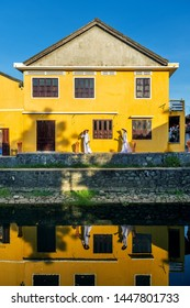 Two Young Vietnamese people wearing white old  costume and traditional hat are walk smiling and talking outdoor on walkway at Old yellow building near Japanese bridge  Hue city, Hoi An, Vietnam.