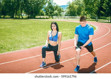 Two young vital people doing stretching relaxing exercises on athletics running track with positive facial expression.
