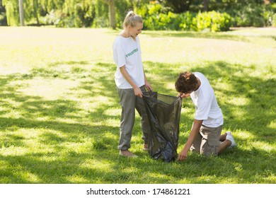 Two young volunteers picking up litter in the park