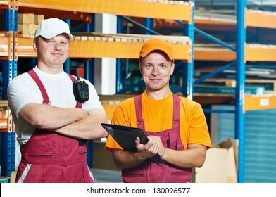 two young warehouse workers men in uniform in front of warehouse rack arrangement stillages