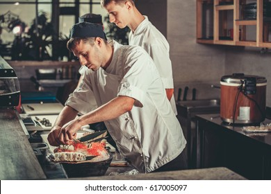 Two young white chefs dressed in white uniform decorate ready dish in restaurant. They are working on maki rolls. Preparing traditional japanese sushi set in interior of modern professional kitchen