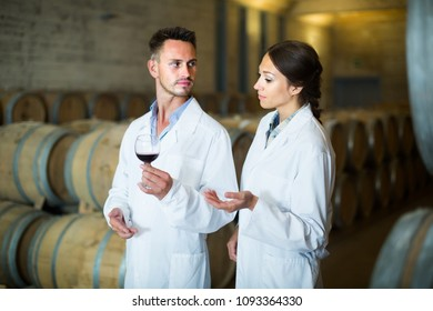 two young winery employees in white coats checking up quality of wine in aging section on winery manufactory