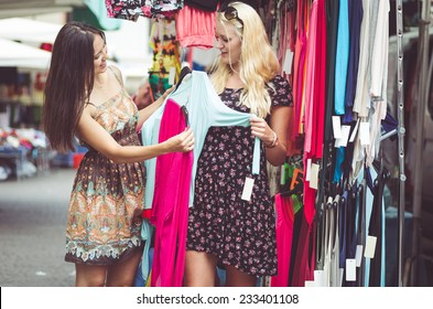 two young woman buying clothes at the city mall