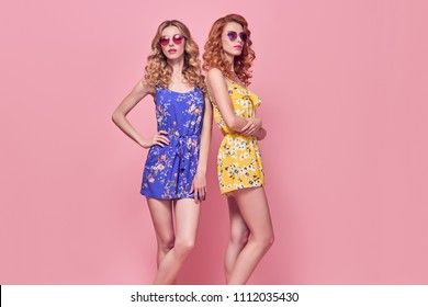 Two Young Woman in Fashion pose. Trendy Floral Dress, Wavy Hairstyle. Glamour Sexy Blond Redhead Model in Stylish Sunglasses, Clutch. Playful Summer Slim Girl on Pink