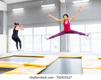 Two young woman friends jumping on a trampoline and doing split indoors