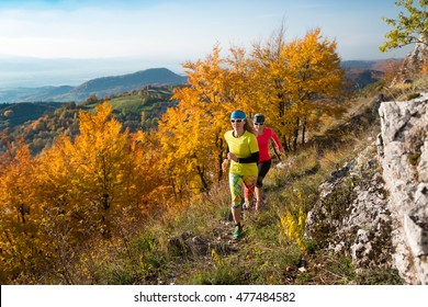 two young woman friends running together on the trail in the autumn mountains with colorful trees
