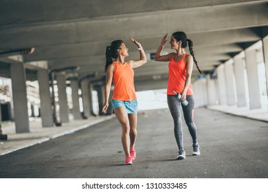Two young woman giving high five to each other.They relaxing after jogging on street.