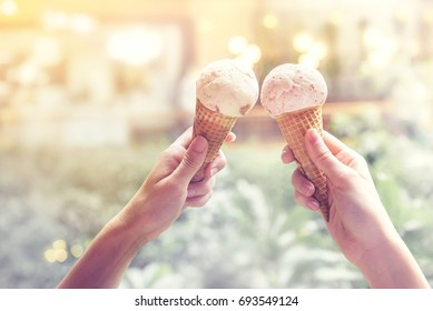 Two young woman hands holding ice cream cones on summer