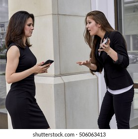 Two young woman in a heated discussion about a broken cell phone