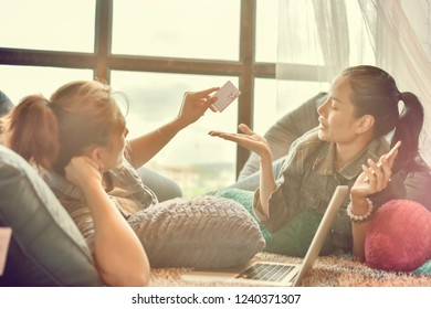 Two Young woman holding credit card and using laptop computer. Online shopping concept.
