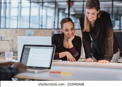 Two young woman at office working on a new creative design. Diverse team of professionals looking at a document smiling.