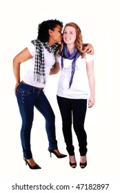 Two young woman, one Hispanic and the other Caucasian, in an portrait in jeans and white top's one kissing the other one, on white background.