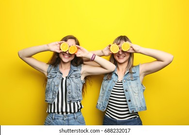 Two young woman with orange fruit on yellow background