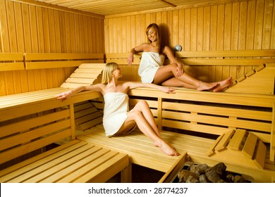 Two young woman in sauna. They looks happy.
