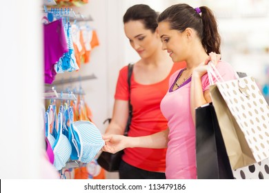 two young woman shopping for lingerie in clothing store