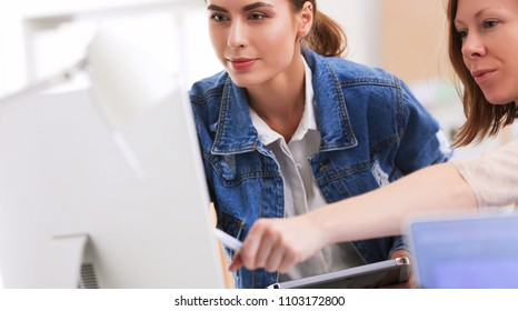 Two young woman standing near desk with instruments, plan and laptop