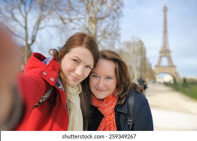 Two young woman taking a self portrait (selfie) near the Eiffel tower