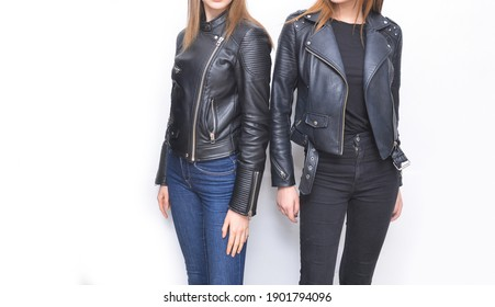 Two young woman wearing black leather jacket and black and blue jeans and black boots .and white shoes