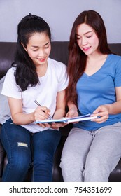 two young woman write a book on sofa in living room at home