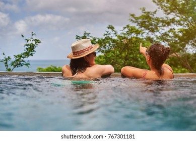 Two young womans in pool view from back