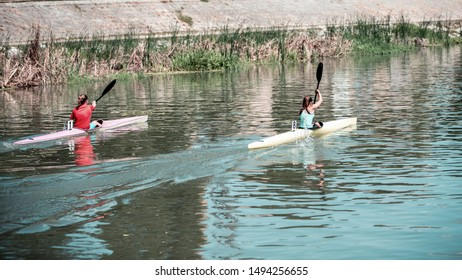 Two young women athletes on rowing kayak on lake during competition