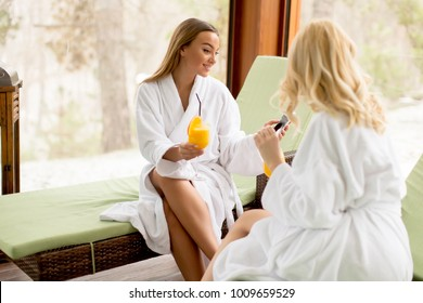 Two young women in bathrobes drinking juice in the spa center