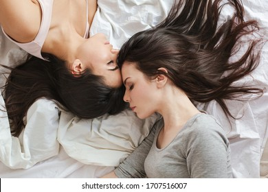 Two young women in bedroom at home lying on bed sleeping heads together calm close-up