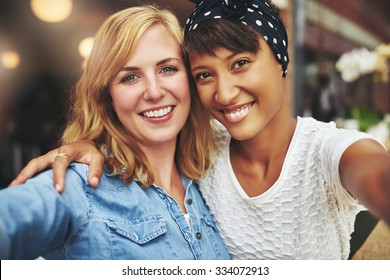 Two young women best friends sitting arm in arm with their faces close together smiling at the camera, multiethnic couple