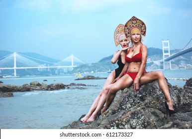 Two young women in bikinis and Russian kokoshniki sit on a stone on the background of the sea