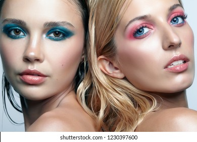 Two young women with blue and pink smoky eues makeup and glossy glitter skin. Closeup shot of blonde and brunette girls. Female friendship concept.