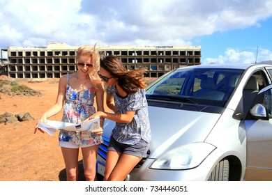 Two young women with car look at road map with old building in background