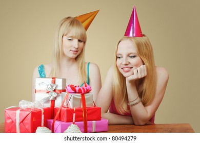 Two young women celebrating birthday. Looking at heap of gift boxes